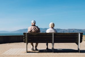 older couple sitting on a bench looking at the landscape