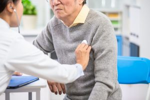 Female doctor uses a stethoscope to examine elderly patient's heartbeat