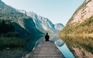 Person sitting on end of dock looking at mountains